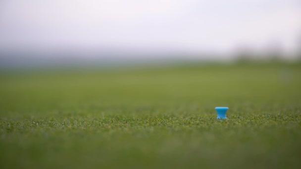Golfista připravuje míček k odpálení na golfovém hřišti