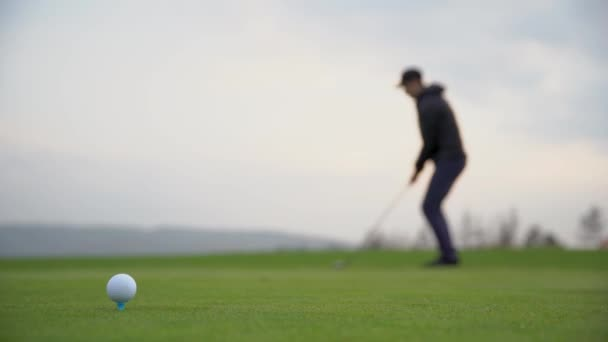 A golf player prepares the ball to be fired at the golf course