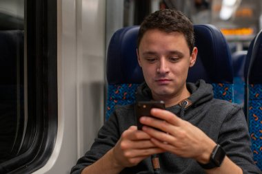 Young man on the train reads news on his smartphone