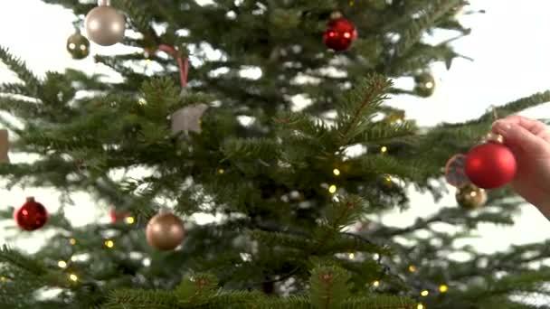 žena zdobí vánoční stromek v předvánočním období