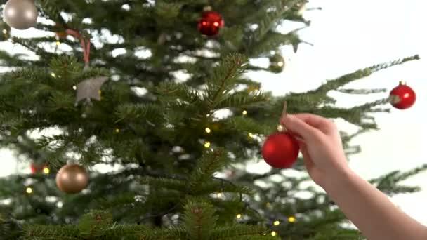 žena zdobí vánoční stromek s červenými kuličkami v předvánoční období