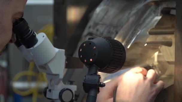 Der Ingenieur überprüft die korrekte Einstellung der Metallform für Gussteile in der Fabrik unter dem Mikroskop