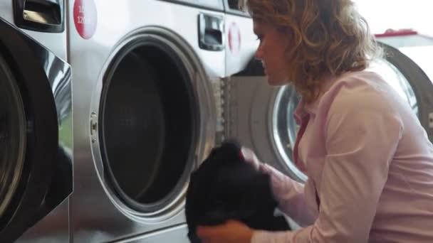 Einbringen von schmutziger Wäsche in die Waschmaschine in der gemeinsamen Waschküche durch eine junge Frau