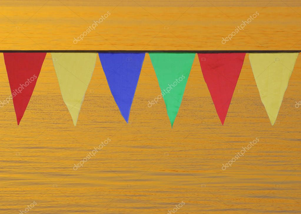 Multi Colored Triangular Flags Hanging in the Sky at an Outdoor on the background of gold water.