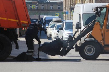 The dump truck poured asphalt crumb into the bucket of the excavator in case of extreme road repairs during the movement of the machines. A worker using a shovel fills a pit on the road from a bucket of an excavator.