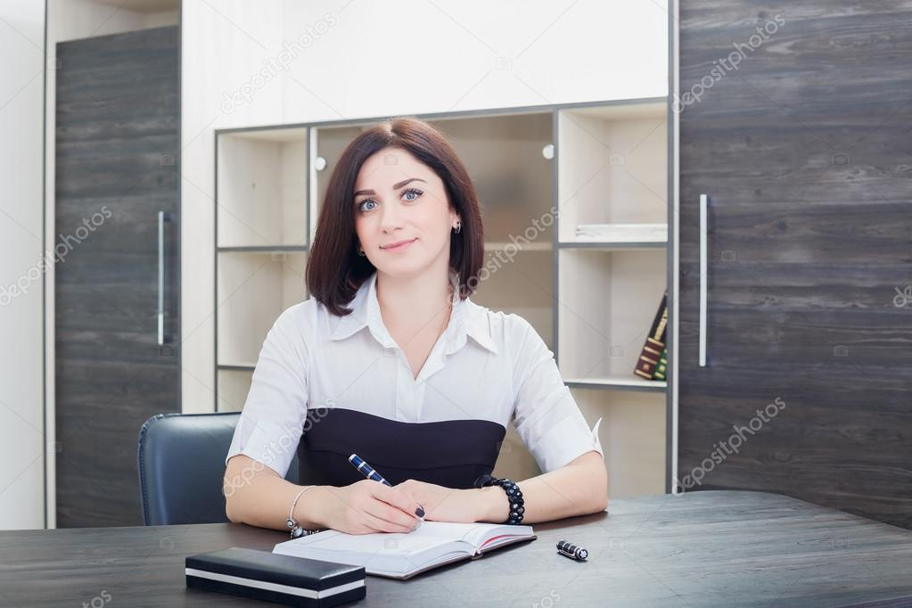 ca21364abf9 Attractive dark-haired woman wearing a black and white blouse sitting at  the desk in the office.– stock image