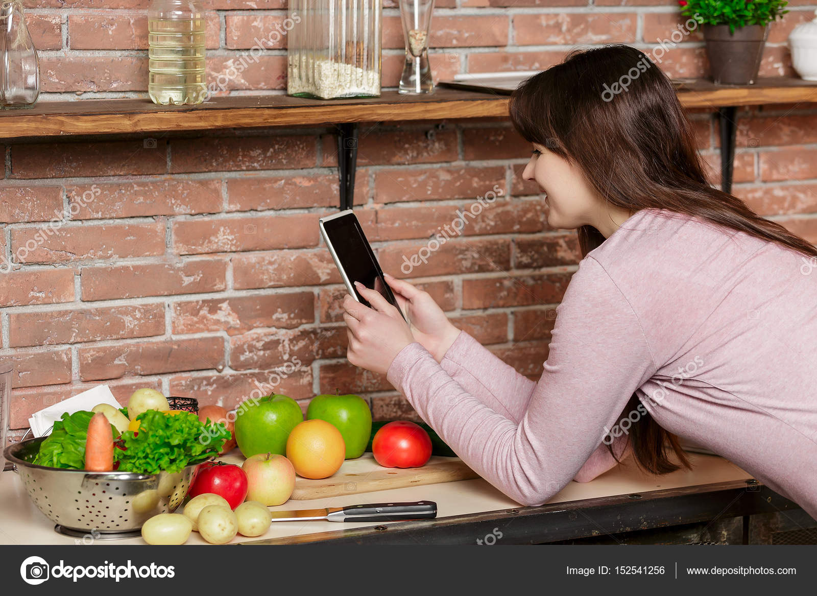 happy woman cooking on kitchen.Woman uses a tablet for online ...