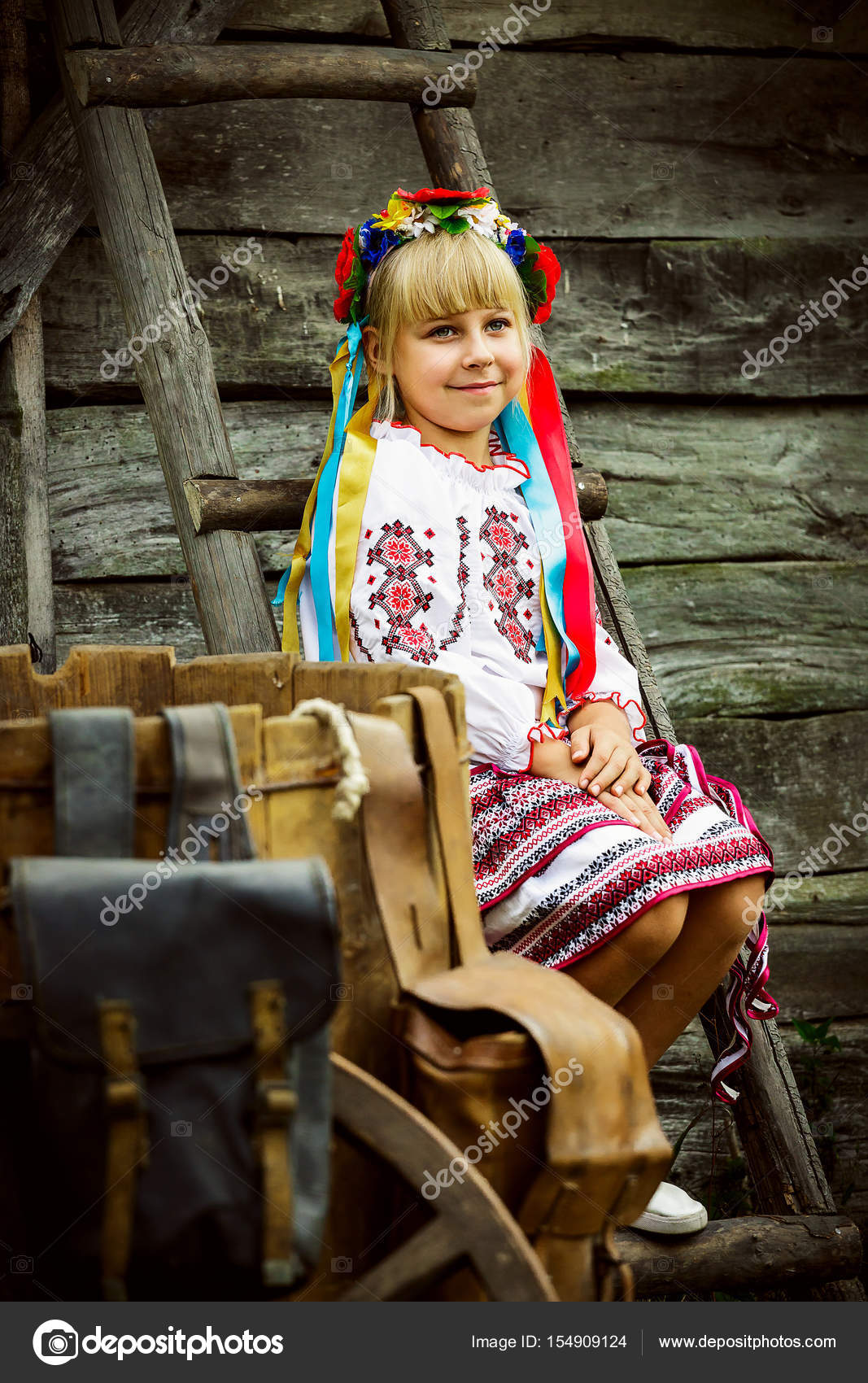 Little Baby Girl In Ukrainian Folk Costume Sits On Stairs