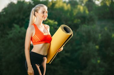 A young blonde in a red top and black pants holds a mat for a fountain in the nature. A woman prepares for gymnastics