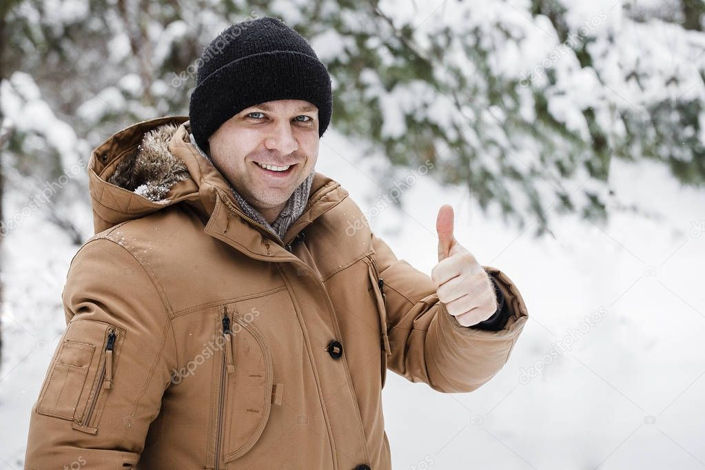 Happy active man showing thumbs up, everything is OK and good. Winter vacation