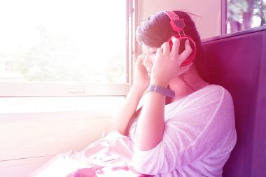 Asian woman listening to music during sitting in a train while t
