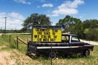 Old truck with a sign for a music event in Luckenbach, Texas, USA.