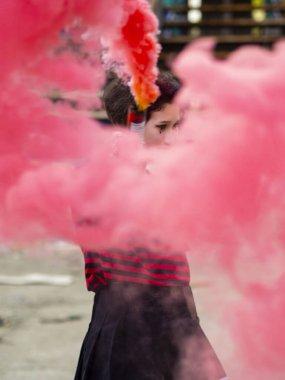 Elinde endüstriyel bir geçmişi olan pembe renkli bir sis bombası olan serseri asi kız. Hipster Ultras taraftarı gençlerin dikey çekimi