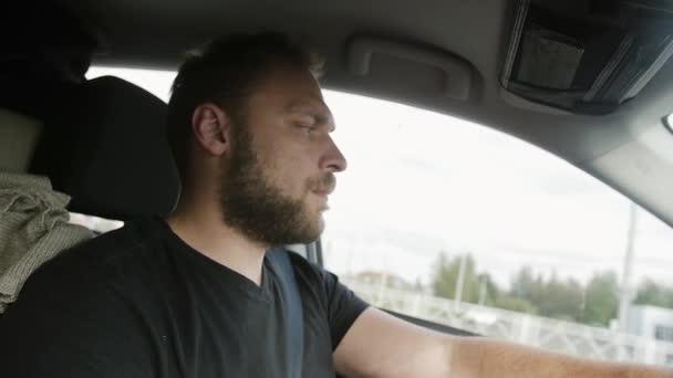Muž řídil auto. Pohledný muž s bradkou v černé tričko jezdí svým autem. Cestování autem