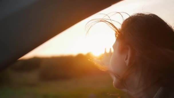 Sunset in the nature. Woman in a car, hand playing in the air. Sunset rays through the trees. Wind blows hair. Slow mo