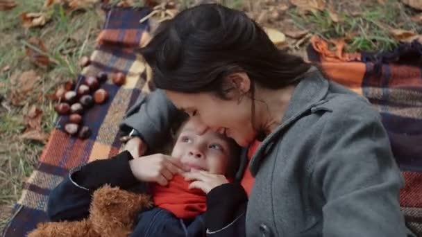 mother with her cute little daughter lying on the plaid Mom tickling and kisses girl in the nose in autumn park 4k