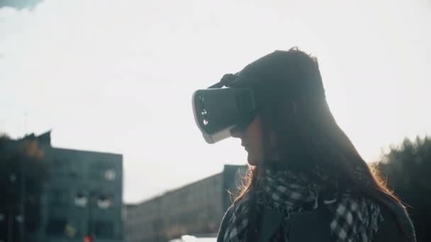Donna castana utilizza le cuffie da realtà virtuale 3d in luce posteriore al tramonto 4k