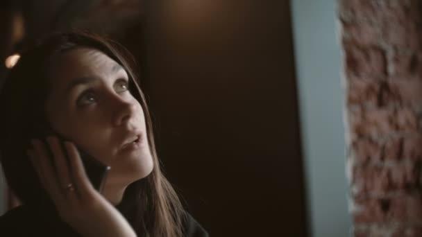 Detailní portrét. Žena mluví o telefonu v kavárně loft 4k
