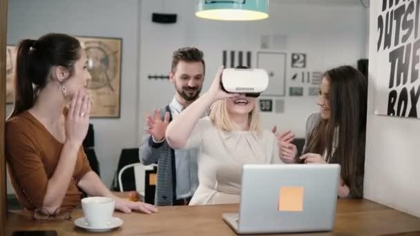 blonďatá dívka se snaží aplikace pro Vr helmu virtuální realita brýle své přátele a kolegy podpořit ji v moderní kanceláři