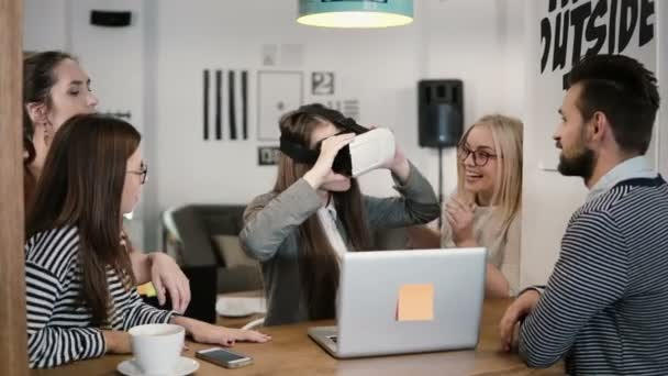 brunette girl tries app for VR helmet virtual reality glasses her friends and colleagues supporting her in modern office