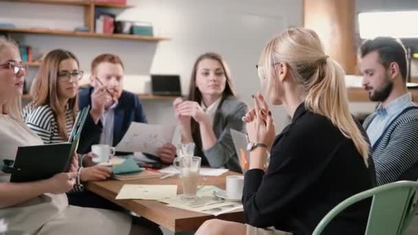 Kreativní podnikání tým u stolu v kanceláři moderní spouštění. Ženské vůdce vysvětluje podrobnosti o projektu.