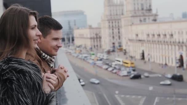 Seitenansicht einer hübschen jungen Frau und eines gutaussehenden brünetten Mannes, die vom Dach aus den Blick auf die Straßen der Stadt genießen
