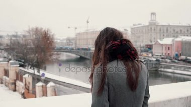 Back view. The sad brunette girl standing on the bridge sighs and looks at the snow-covered winter town.