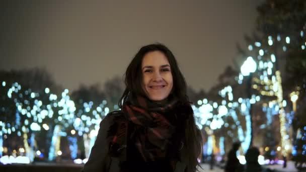 atraktivní žena v zasněžené vánoční noci úsměv na kameru před stromy parku zdobené světélek
