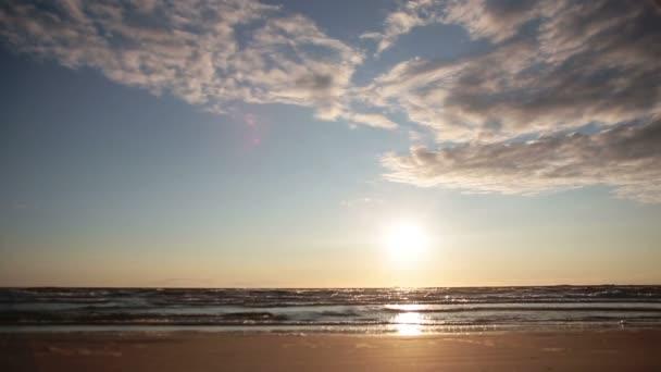 ein wunderschöner ruhiger Strand bei Sonnenuntergang, wenn die Wellen im Sonnenlicht funkeln.