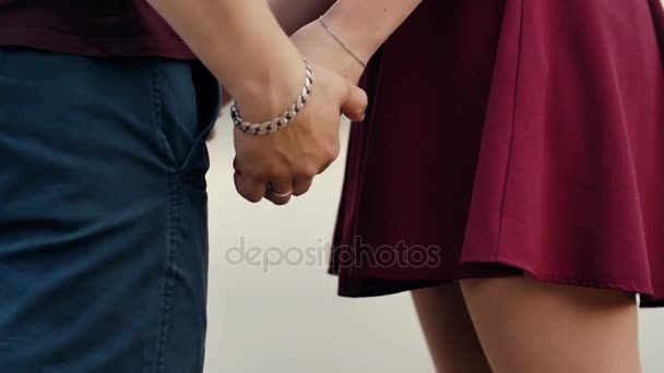 Close-up of lovers hands. Couple in love are standing holding hands. Both are in dark red clothes. Slow mo