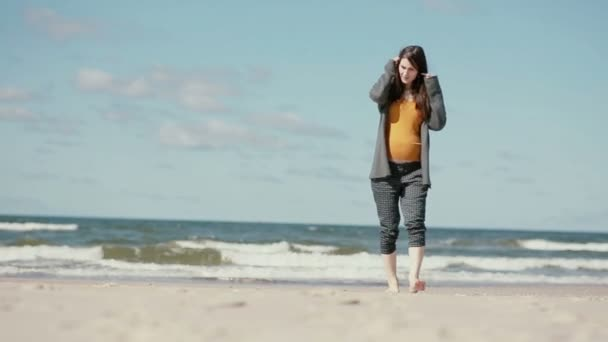A pregnant dark-haired young woman is walking barefoot along a sandy beach slowly approaching the camera.
