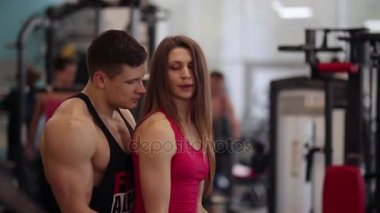 Pretty woman lifts dumbbells while working out in the gym. Athletic man is helping her to do the exercise correctly.
