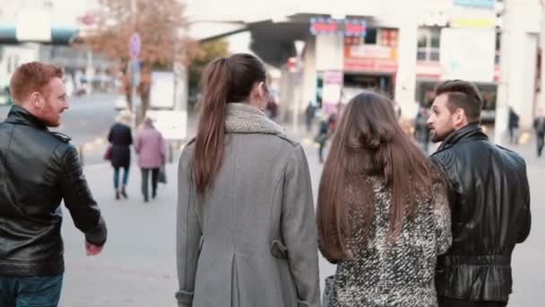 Back view of friends walk at the street. Handsome men and two pretty girls chatting on the go. Steadicam shot, slow mo