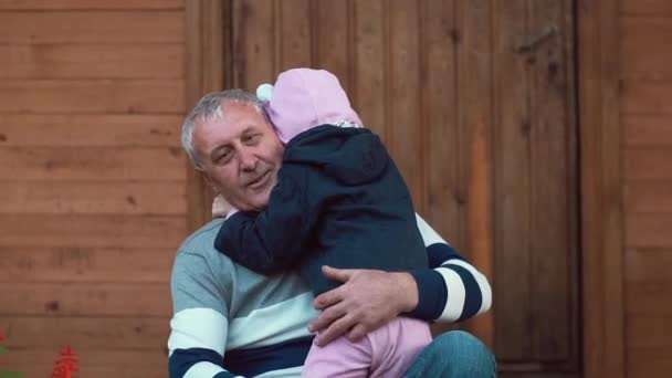 An ageing man is having great time with his grandchildren. He hugs them, they run into his embrace. Slow mo