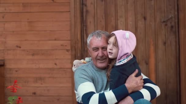 An old man embraces his little granddaughter. The girl looks into camera, smiles and talks to her grandfather. Slow mo