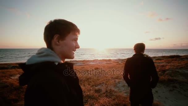 Dva mladí muži čekají na písečných dunách na pláži si užívat výhled nádherný západ slunce
