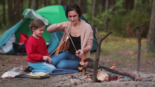 Šťastná rodina spolu s skvělý čas v přírodě. Máma učí dceru vařit marshmallows na otevřeném ohni