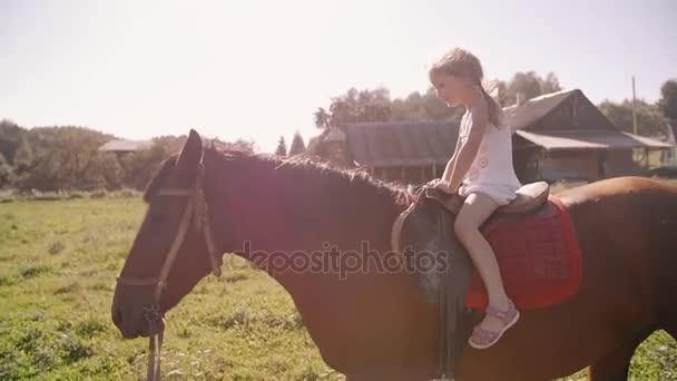A boldog kicsi lány lovaglás a természetben egy napsütéses napon. Ő mosolyogva, szórakozás. Lassú mo