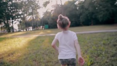 A cheerful little girl runs away from camera in the nature on a sunny summer day. Back view, slow mo