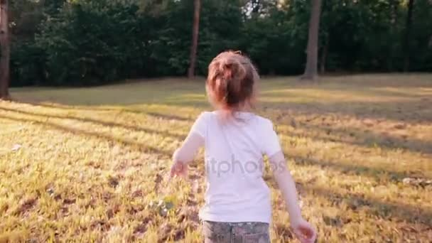 Ein fröhliches kleines Mädchen läuft an einem sonnigen Sommertag in einem Park vor der Kamera davon. Rückansicht, langsam