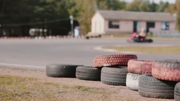 Kart drivers moving on a go kart track  Coloured tires near the track