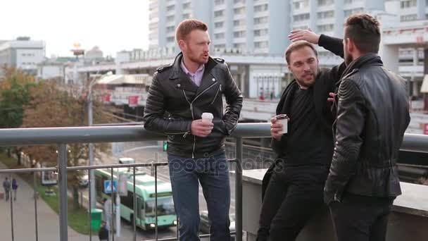 Three young handsome men with beards have conversation on a bridge railing. Good-looking guys talk, have coffee. Slow mo