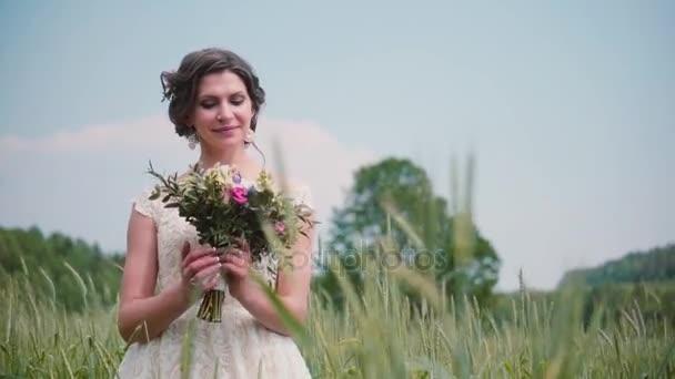 Krásná mladá nevěsta při pohledu na její svatební kytice v pšeničné pole. Pěkně krajkové svatební šaty na ni