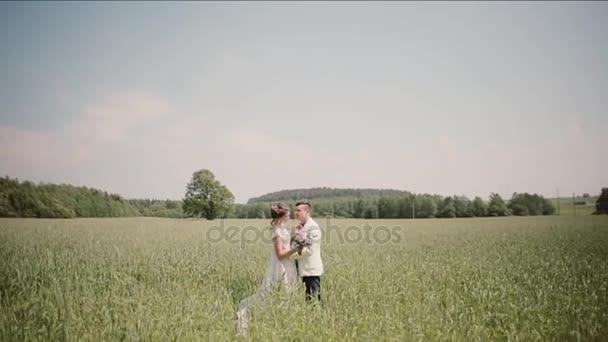 Boční pohled na pár stojící blízko sebe v pšeničné pole na jejich svatební den. Nevěsta a ženich v svatební šaty