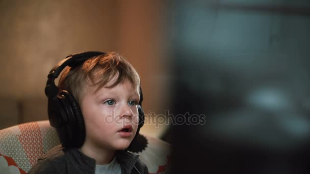 little boy in big headphones carefully watching something on a computer monitor sitting in a chair