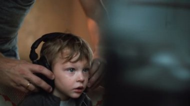 Father straightens big headphones on a little boy who looks attentively something on a computer monitor sitting in chair