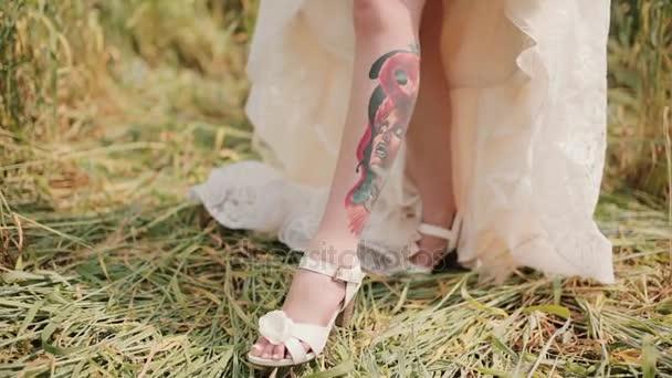 A menyasszony egy tetoválás a lábát egy esküvői ruha alatt látható. Meglepő képe egy színes tetoválás egy képet egy nő