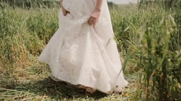 Menyasszony látható színes tetoválás a lábát. Ő felemeli a ruháját, és elkezdi sétál a búza mező
