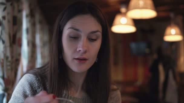 Mladá bruneta atraktivní žena sedí v kavárně, mluvit a jíst lžící. Dívka při konverzaci s někým