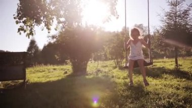 Beautiful cute brother and sister playing outdoor. Girl swinging, boy walking on the grass.